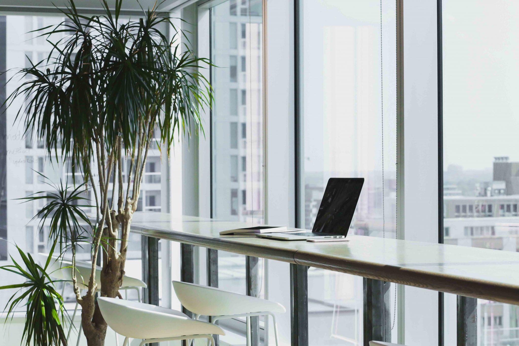 scrivania con laptop e vetrata sullo sfondo