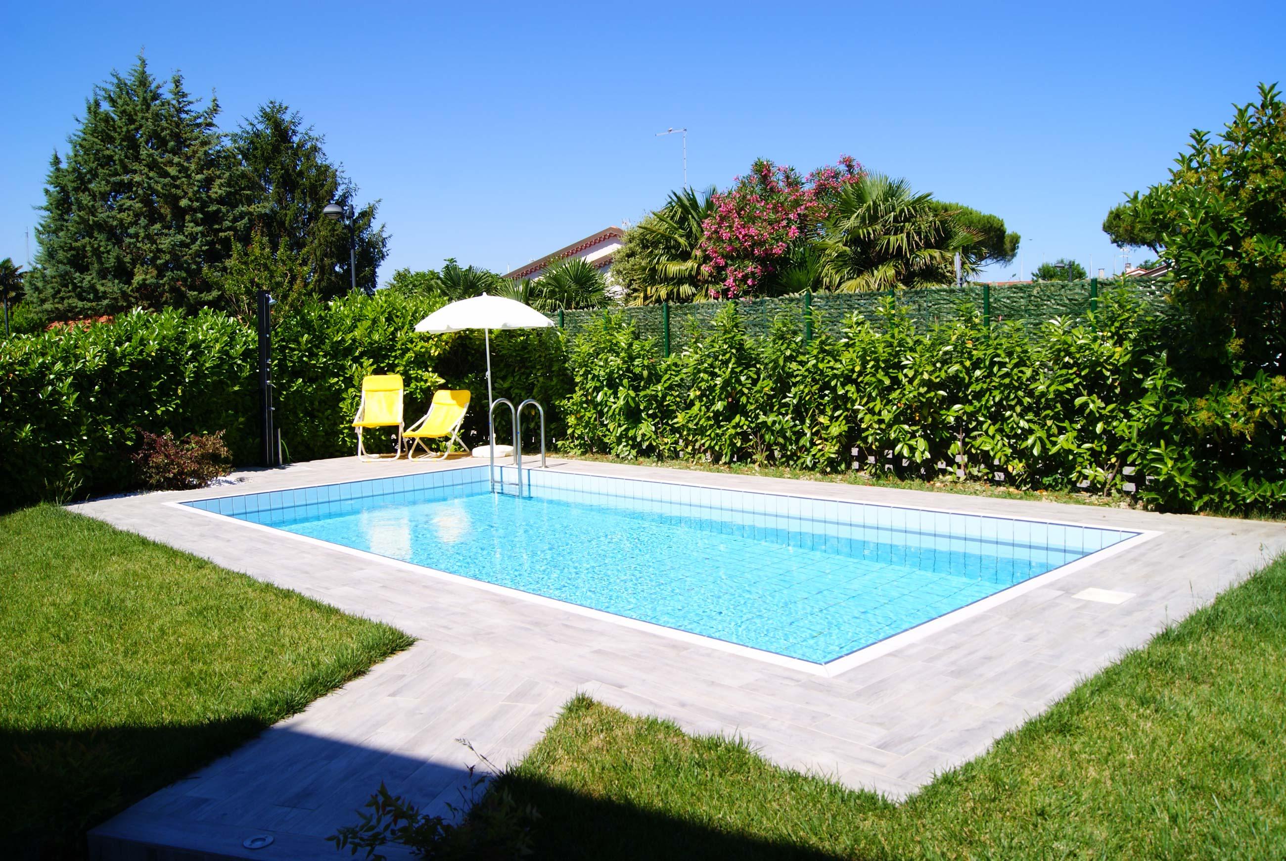 giardino con piscina, sedie a sdraio con ombrellone e doccia