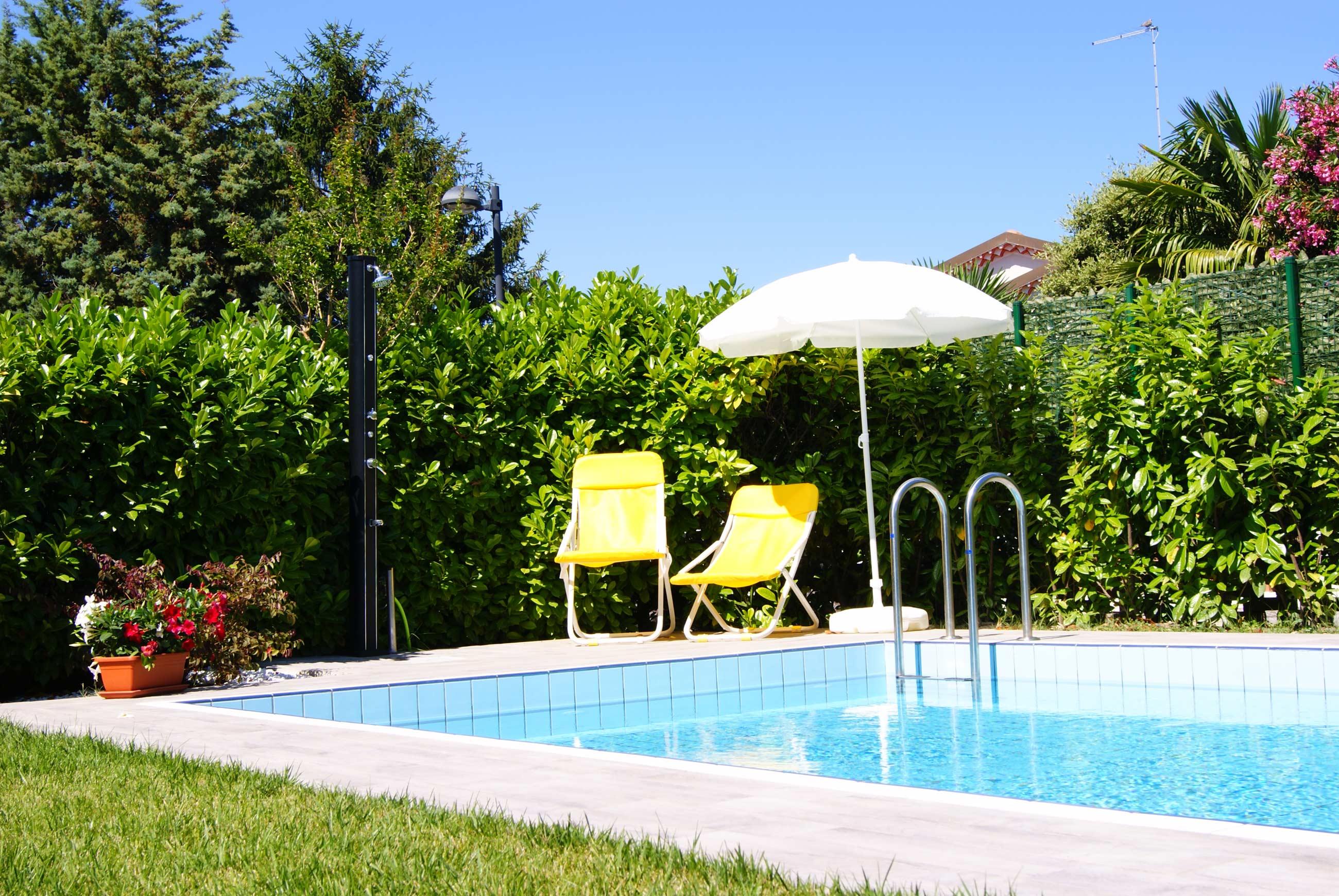 particolare di una piscina con sedie sdraio, ombrellone e doccia esterna